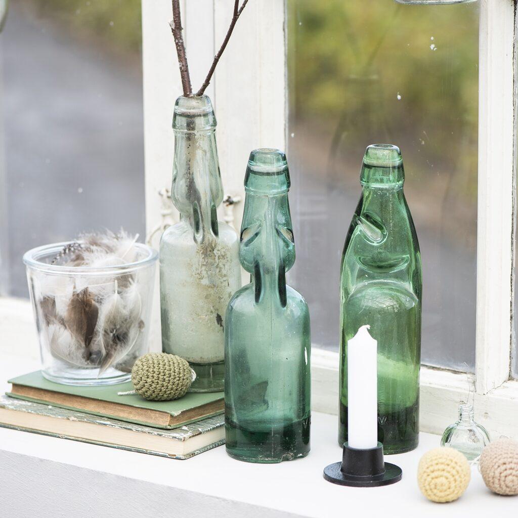 Alte Soda-Flaschen und eine Kerze auf einer Fensterbank
