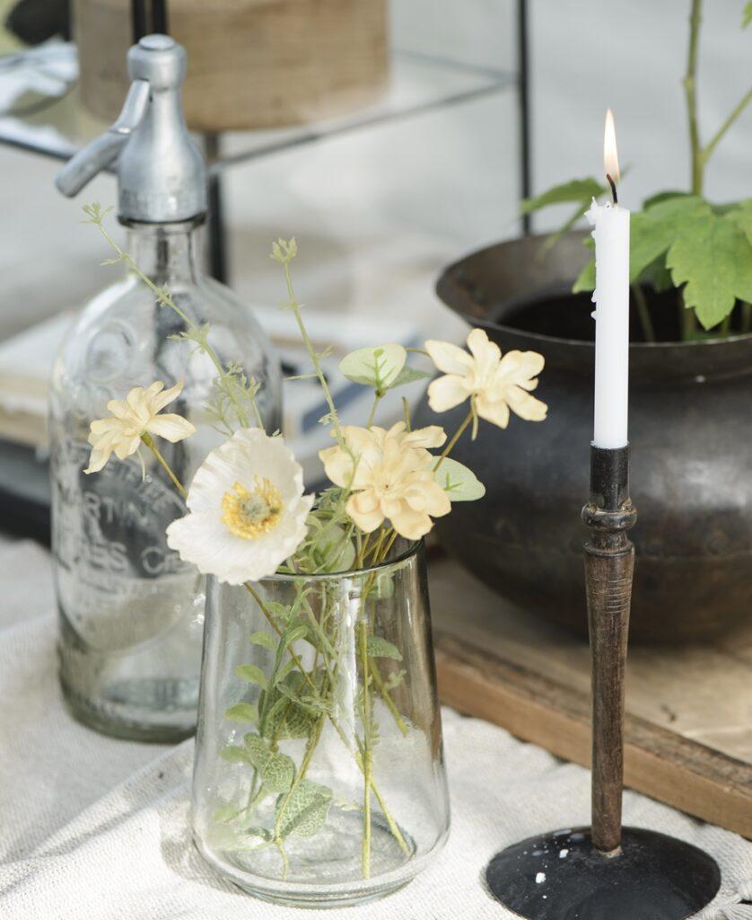 Deko-Arrangement mit Blumen und Kerzen