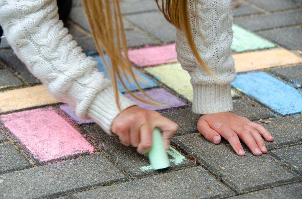 Kind malt mit Straßenmalkreide