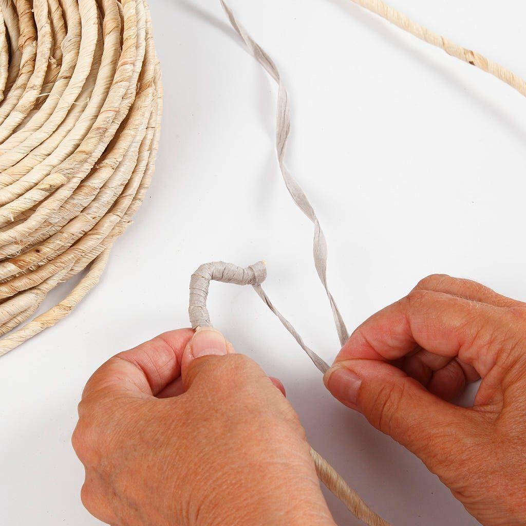 Maisschnur wird mit Papierbast umwickelt