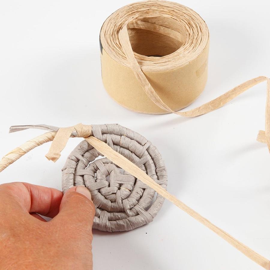 Eine Spirale aus Papierbast wird angefertigt