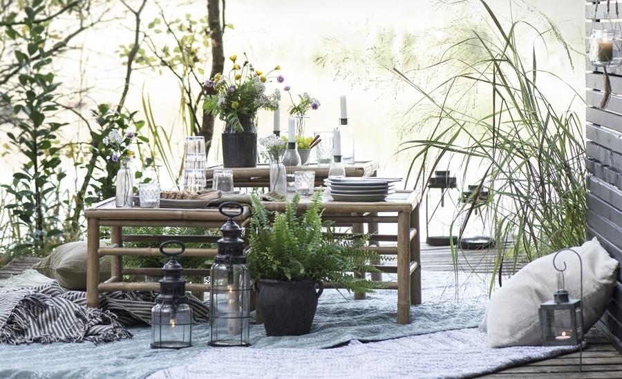 Terrasse mit Tisch, Pflanztöpfen und Laternen