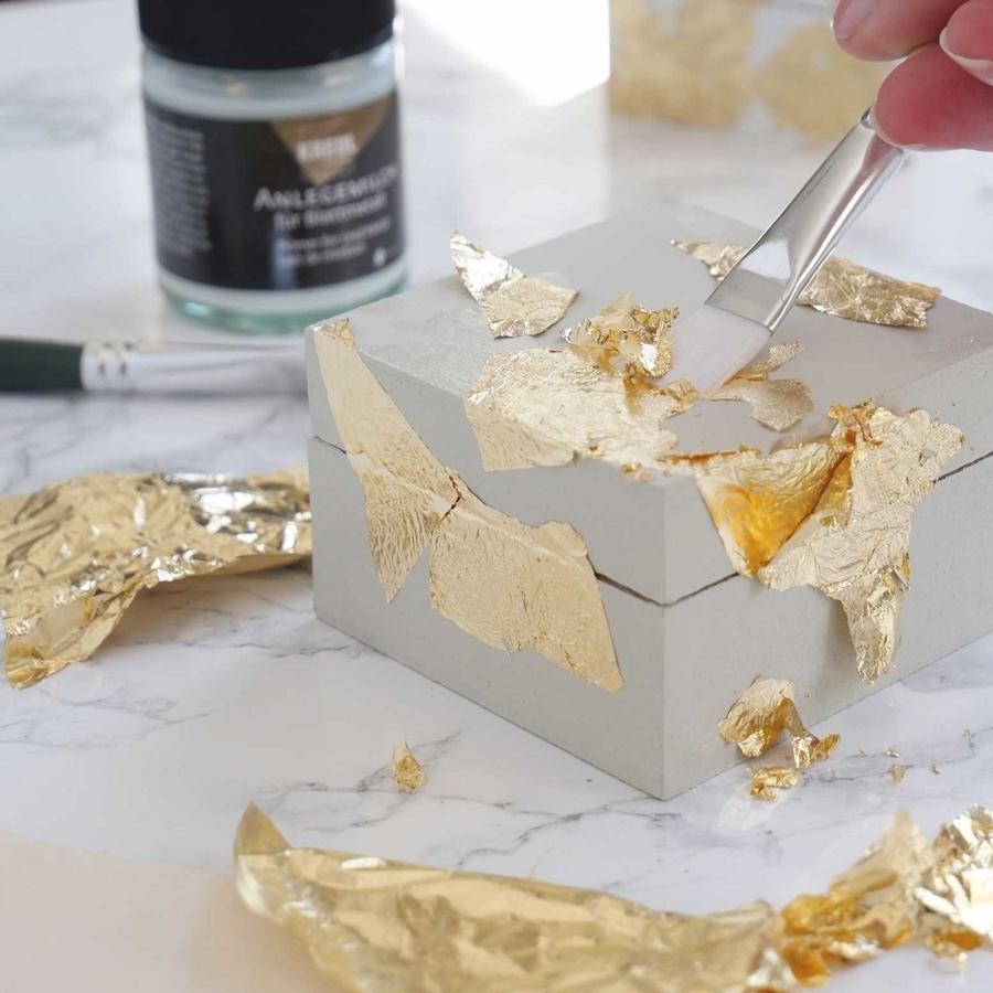 Blattmetall in gold wird auf eine Schachtel aufgetragen
